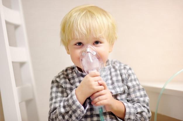 吸入器のマスクによるかわいい男の子吸入療法。呼吸器の問題や喘息の小さな子供の画像を閉じます。明確な酸素マスクを持つ病気の男の子。 Premium写真