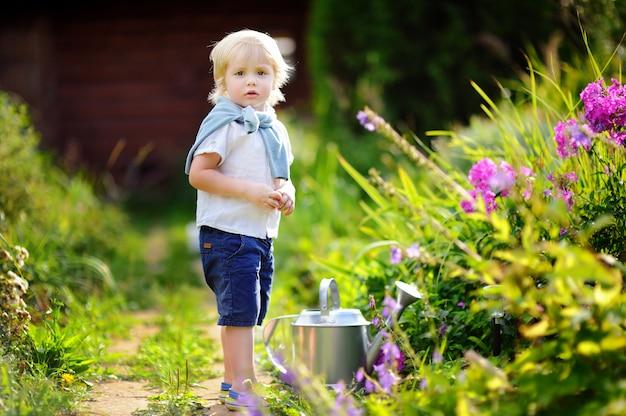 夏の晴れた日に庭の植物に水をまくかわいい幼児男の子。国内の庭の園芸工具を持つ小さな子供 Premium写真