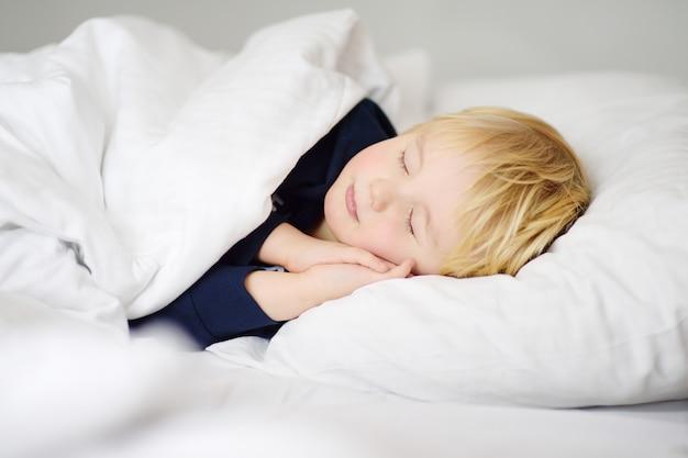 眠っているかわいい男の子。疲れた子供が親のベッドで昼寝をしています。 Premium写真