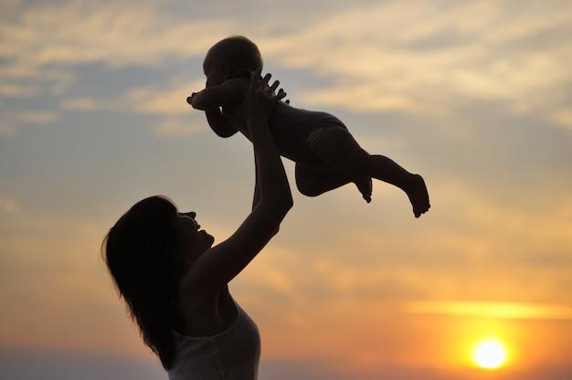 Портрет молодой женщины с маленьким ребенком как силуэт у воды Premium Фотографии