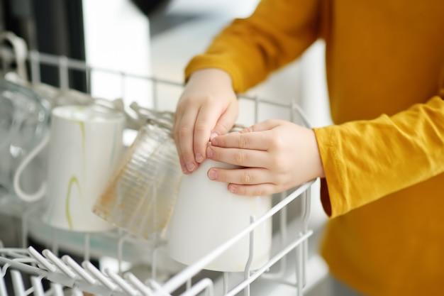 子供が家庭の食器洗い機に汚れた食器を置きます。閉じる。 Premium写真