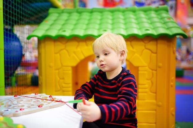 プレイセンターで教育玩具を楽しんで幸せな男の子 Premium写真