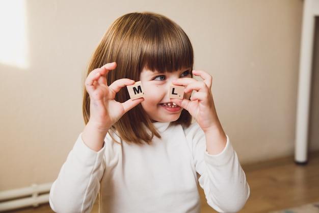 Маленькая кавказская девушка держа деревянные письма перед ее лицом. раннее развитие концепции ребенка. Premium Фотографии