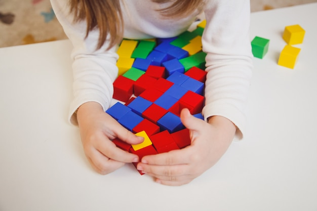 Руки ребенка с красочными кубиками на белой таблице. ребенок играет за столом. раннее развитие концепции ребенка. Premium Фотографии