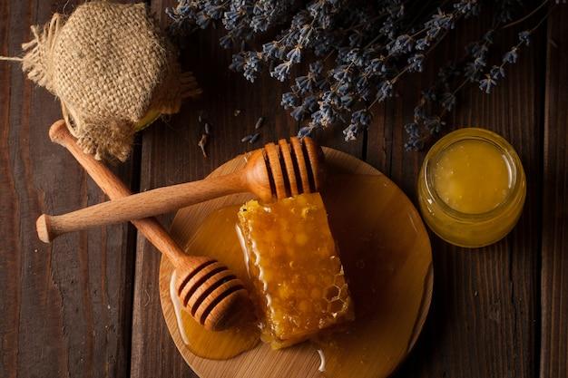蜂蜜ディッパーとハニカム。ナッツとリンゴの蜂蜜とさまざまな種類のナッツ Premium写真