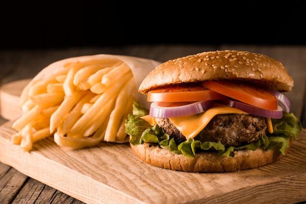 Домашний гамбургер с говядиной, луком, помидорами, листьями салата и сыром. свежий бургер заделывают на деревянный деревенский стол с картофелем фри, пиво и чипсы. чизбургер. Premium Фотографии