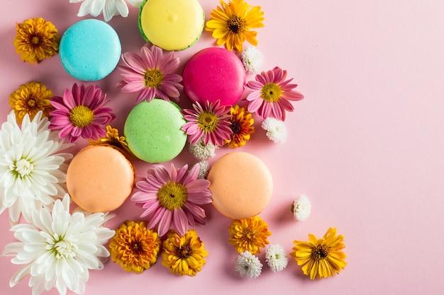 花、明るい背景にお茶を一杯のギフトボックスにケーキマカロンの静物と食べ物の写真。マカロンのお菓子とデザートのコンセプト。 Premium写真