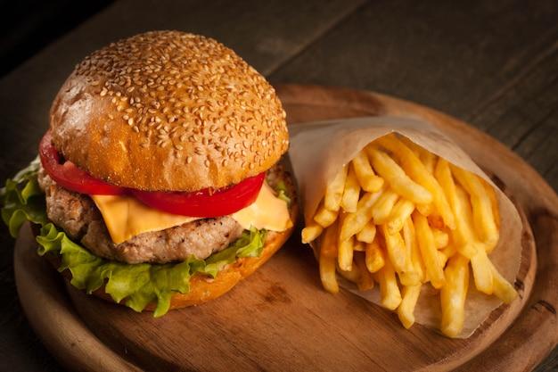 Домашний гамбургер с говядиной, луком, помидорами, листьями салата и сыром. Premium Фотографии