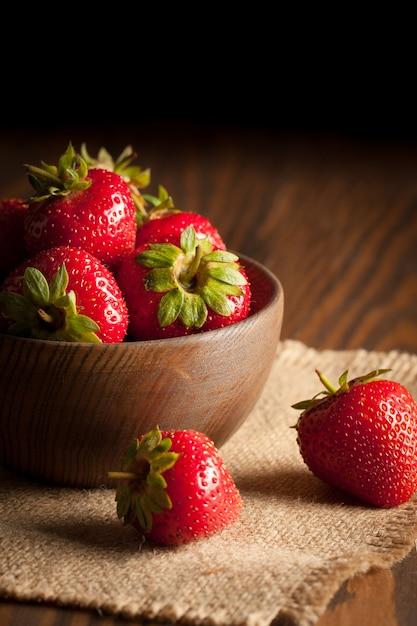 素朴な背景に木製のボウルに新鮮な熟した赤いイチゴのマクロ写真。オーガニック天然物。 Premium写真