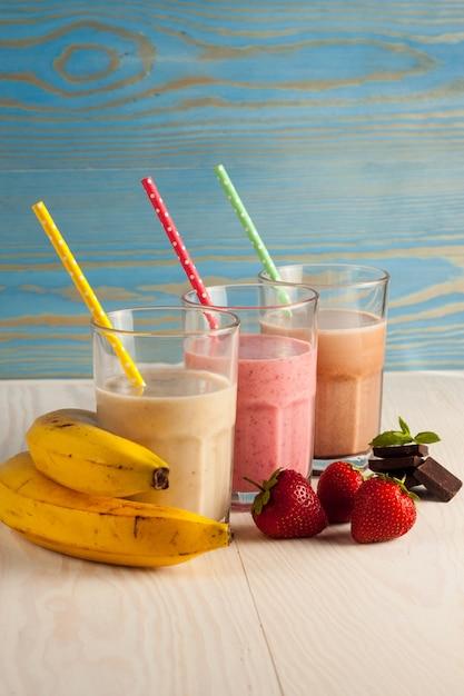 Длинные стаканы молочных коктейлей с шоколадом, клубникой, бананом, с мороженым на белом Premium Фотографии