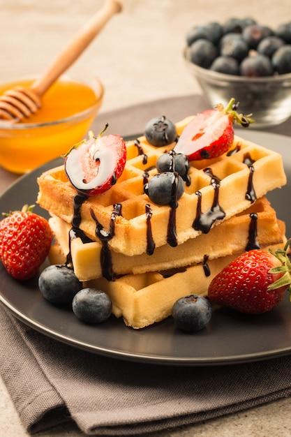 Бельгийские вафли с медовой черникой и клубникой Premium Фотографии