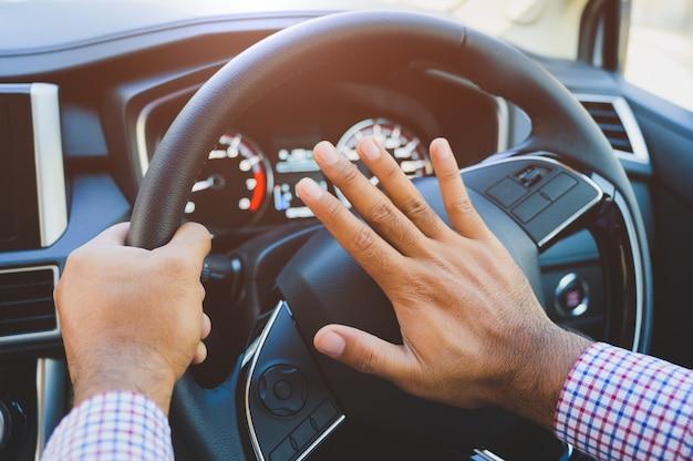 Рука человека толкает автомобильный гудок во время вождения автомобиля Premium Фотографии