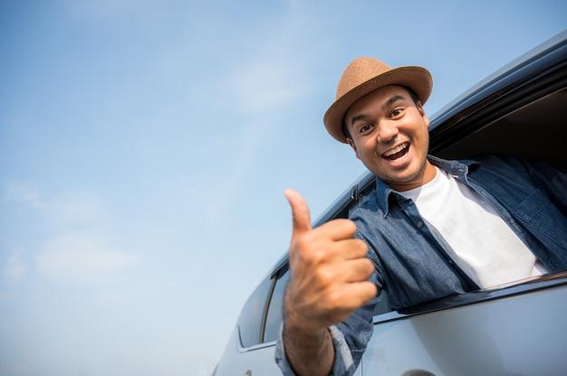 アジア人男性は帽子をかぶり、青いシャツは運転して親指を立てます。 Premium写真