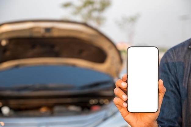 故障車の近くのスマートフォンの空白の画面 Premium写真
