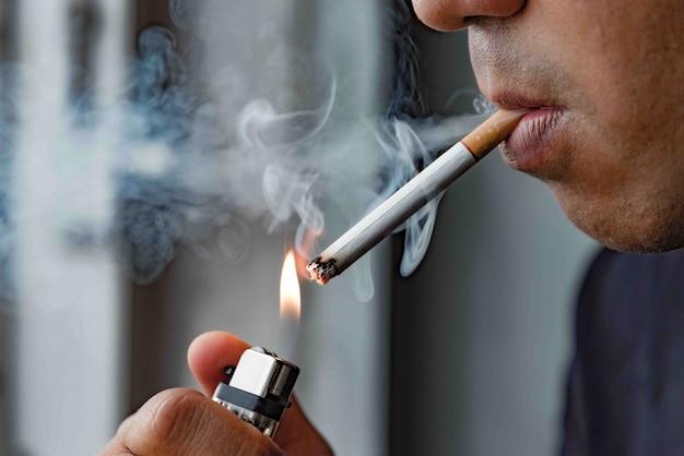 タバコを吸う若い男を閉じます。 Premium写真