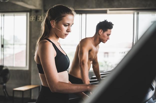 若いカップルトレッドミルで実行して運動常に健康を維持するために Premium写真