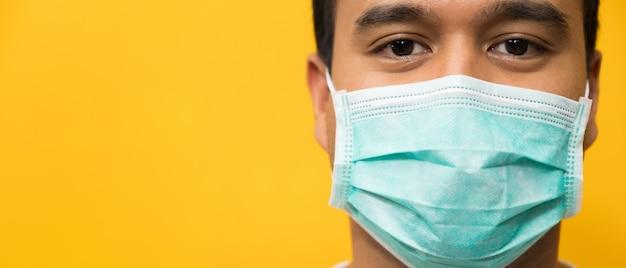 黄色のコロナウイルスに対する保護フェイスマスクを着ている若いアジア人を閉じる Premium写真