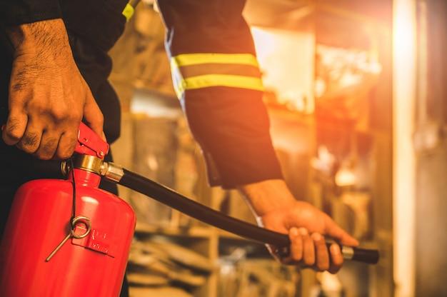 消火器の戦いを使用して手の消防士を閉じます。 Premium写真