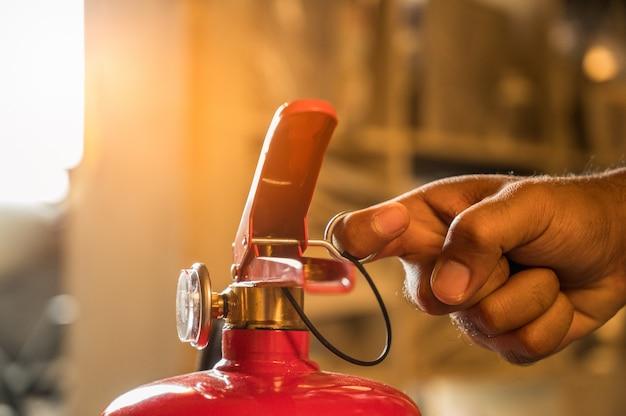 消火器の戦いを使用して手の消防士を閉じます。消火器の引き手 Premium写真