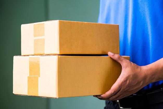 Конец вверх работник доставляющий покупки на дом в голубых формах держа пакет картонную коробку. Premium Фотографии