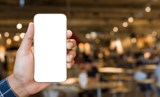 空白のスマートフォンの男性の手を示す Premium写真