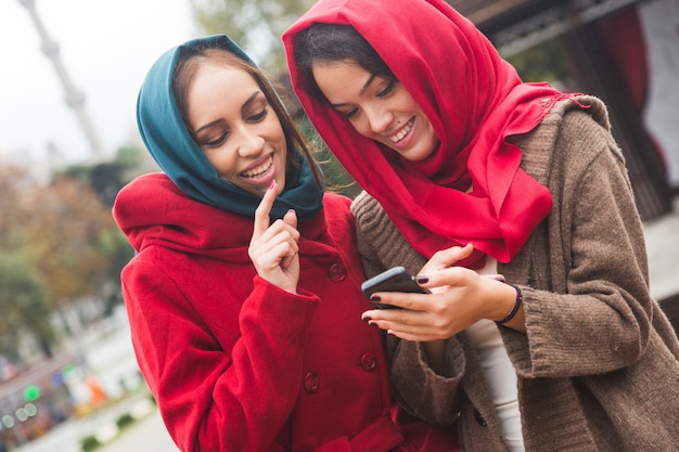イスタンブールでスマートフォンを使用してベールを着ているアラブ女性 Premium写真