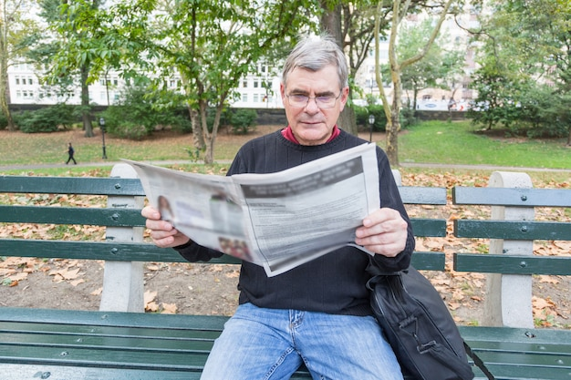 Газета чтения старшего человека на парке Premium Фотографии