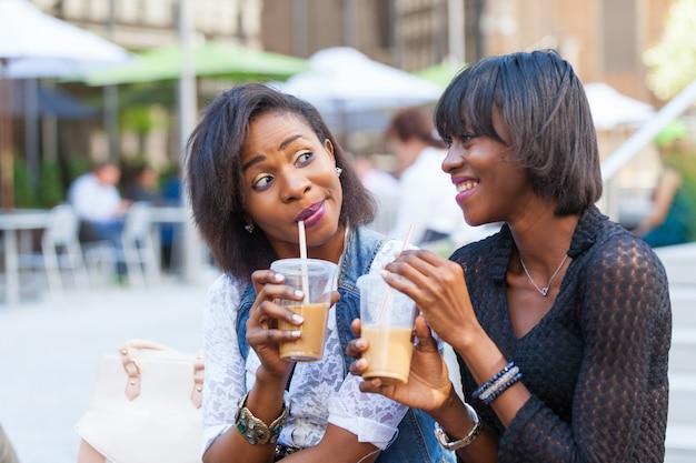 Две красивые темнокожие женщины наслаждаются освежающими напитками в нью-йорке Premium Фотографии