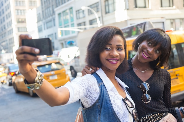 Две красивые темнокожие женщины, делающие селфи в нью-йорке Premium Фотографии
