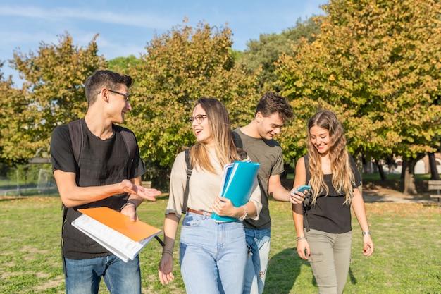 Счастливые студенты в парке с книгами и с удовольствием Premium Фотографии