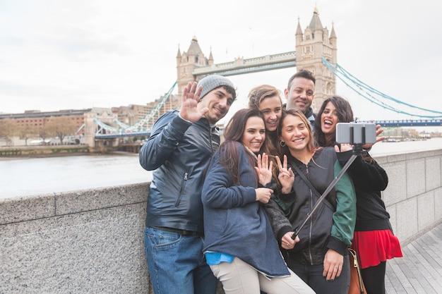 Группа друзей, наслаждаясь принимая селфи в лондоне Premium Фотографии
