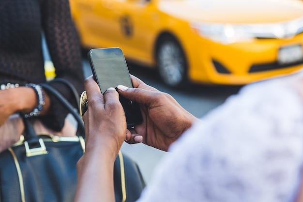 Две красивые темнокожие женщины, использующие смартфон в нью-йорке Premium Фотографии