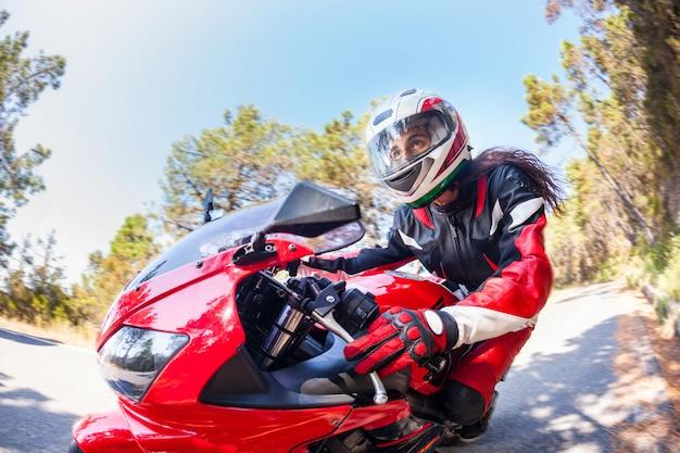 Женщина за рулем мотоцикла по сельской дороге Premium Фотографии
