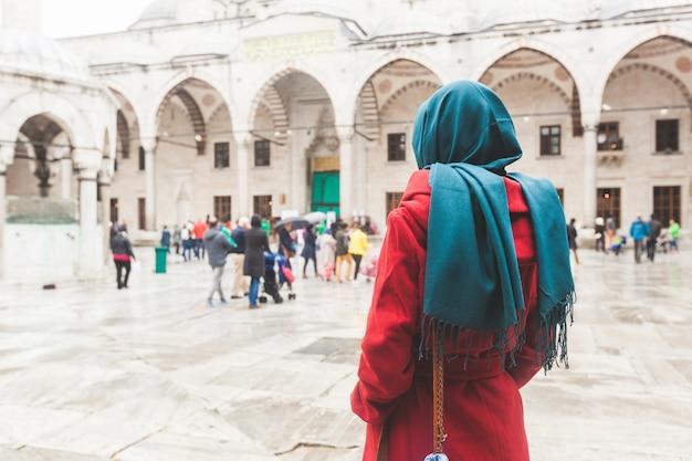 モスクの前にベールを着ている若いアラビア女性 Premium写真