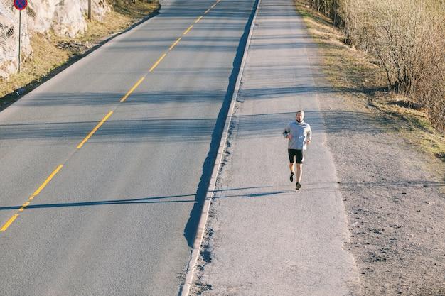 空の山道に沿って外を走っている若い男 Premium写真