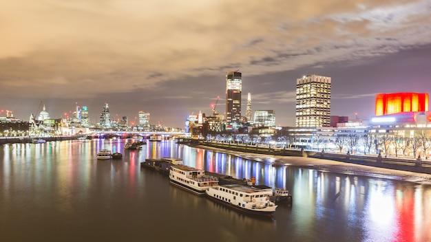 夜のボートや高層ビルのロンドンビュー Premium写真