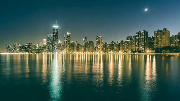 反射と夜のシカゴのスカイライン Premium写真