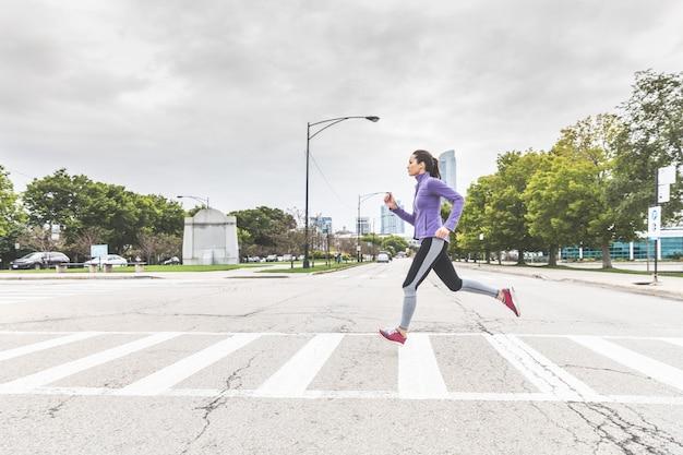 ジョギングやシカゴのシマウマの道を渡る女性 Premium写真