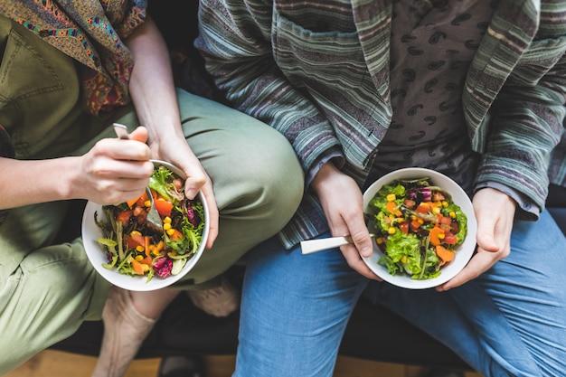 自宅で健康的なサラダを食べるカップルソファー Premium写真