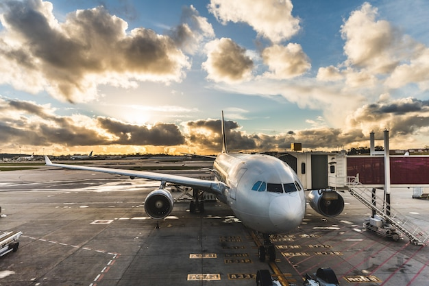 夕暮れ時の空港で飛行機に乗る人 Premium写真