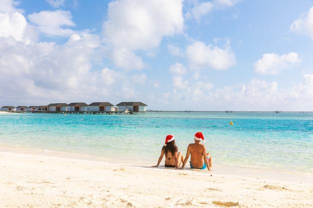 海辺でリラックスしたクリスマスサンタ帽子をカップルします。 Premium写真