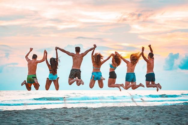 Счастливые успешные друзья прыгают на пляже Premium Фотографии