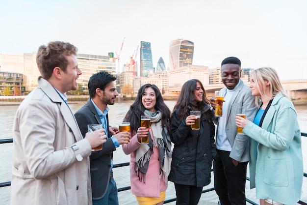 Счастливые бизнесмены пьют пиво после работы в лондоне Premium Фотографии