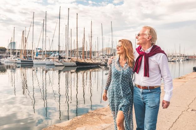 バルセロナの港の近くを歩く年配のカップル Premium写真