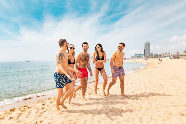 バルセロナのビーチで楽しんで幸せな友達 Premium写真