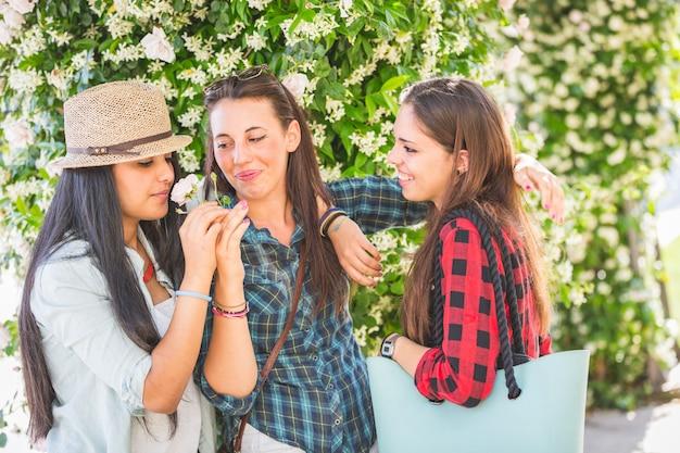 Три девушки пахнущие цветок Premium Фотографии
