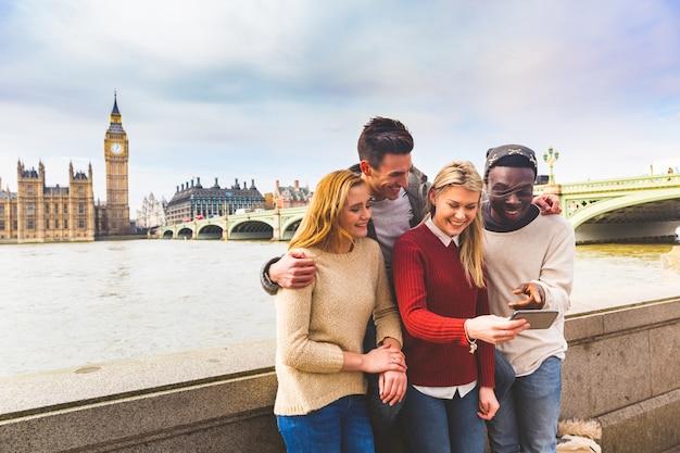 Друзья веселятся со смартфоном в биг бен в лондоне Premium Фотографии