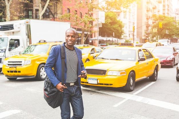 Черный человек, пересекая улицу в нью-йорке. Premium Фотографии