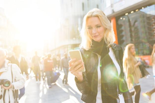 ロンドンでスマートフォンを見ている金髪の女性 Premium写真