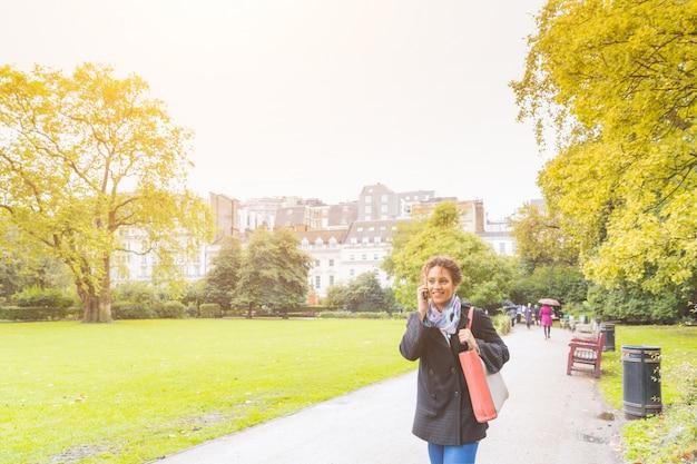 ロンドンの公園で電話で話している若い女性 Premium写真